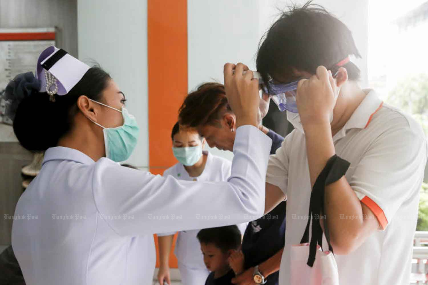Nurses check the body temperature of people arriving at King Mongkut's Institute of Technology North Bangkok on Wednesday, looking for signs of novel coronavirus infection. (Photo: Pattarapong Chatpattarasill)