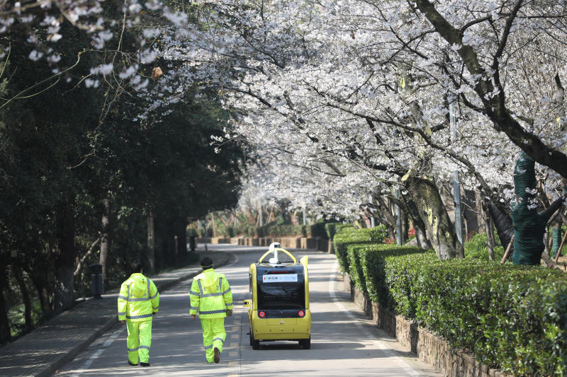 Security personnel walk next to a 5G enabled autonomous vehicle, installed with a camera filming blooming cherry blossoms for an online live-streaming session, inside Wuhan University in Wuhan on Tuesday. (China Daily via Reuters photo)
