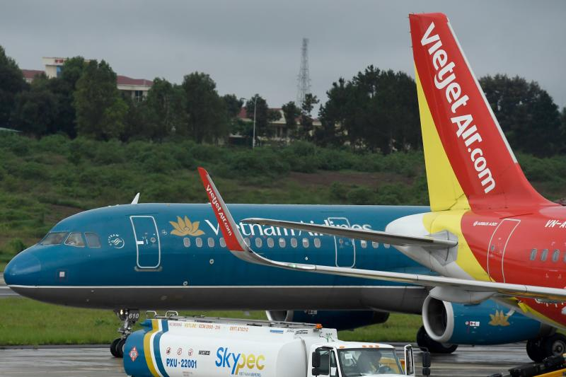 This file picture taken on July 29, 2018 shows passenger jets from Vietnam's two major airlines, Vietnam Airlines and Vietjet, on the tarmac at Pleiku airport in the Central Highlands. (AFP photo)