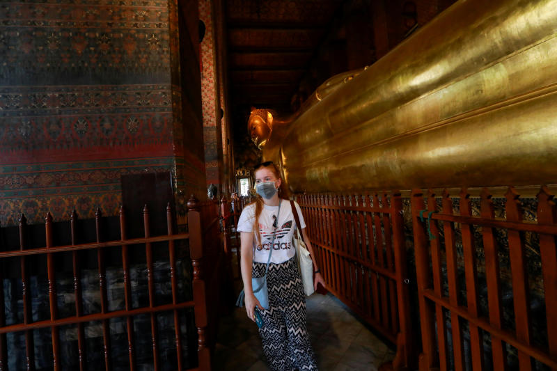 A tourist wears a protective mask on Monday at Wat Pho, a temple which is usually full of tourists, amid fears of coronavirus. (Reuters photo)