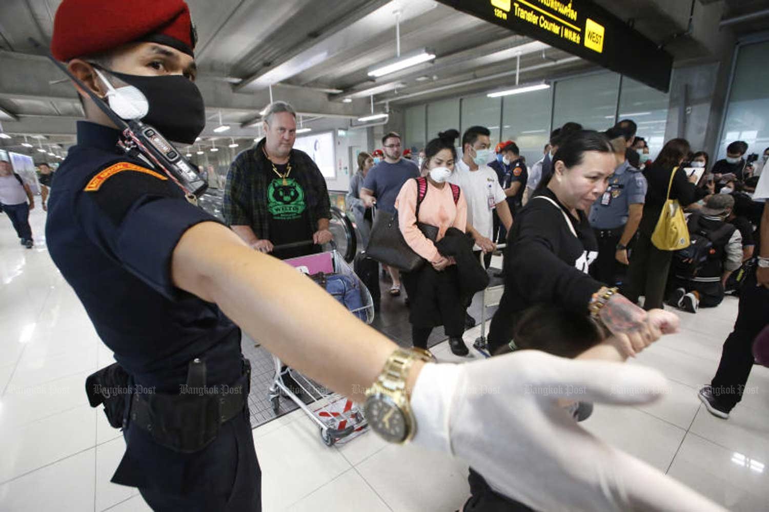 A security official directs arriving travellers at Suvarnabhumi airport last Thursday. (Photo: Pornprom Satrabhaya)