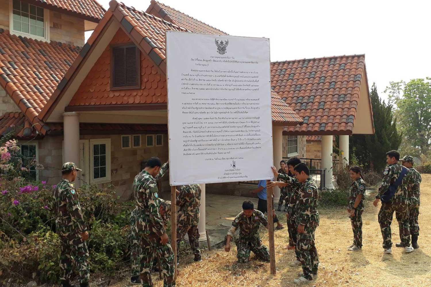 Erawan National Park officials post a demolition order at the resort owned by a former managing director of Thai Diary Industry Co in Sri Sawat district, Kanchanaburi province, on Feb 28. (File photo)