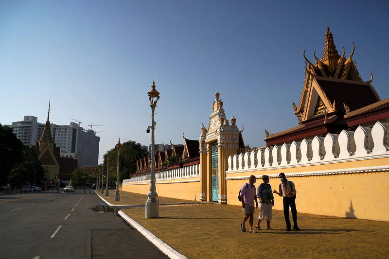 Tourists walk with a guide outside the Royal Palace which has being closed for visitors as precaution against the coronavirus outbreak in Phnom Penh on Thursday. (Reuters photo)