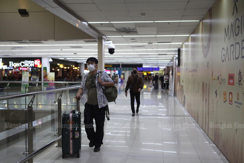 A traveller wearing a face mask at Don Mueang airport on Friday. (Photo by Arnun Chonmahatrakool)