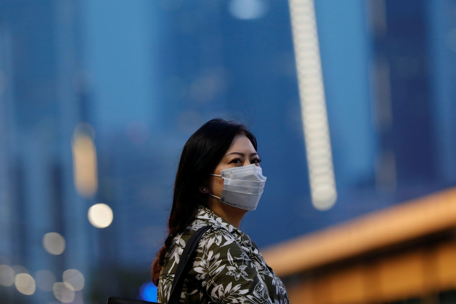 A woman wearing a protective face mask stands on the sidewalk amid the spread of coronavirus disease in Jakarta on Thursday. (Reuters photo)
