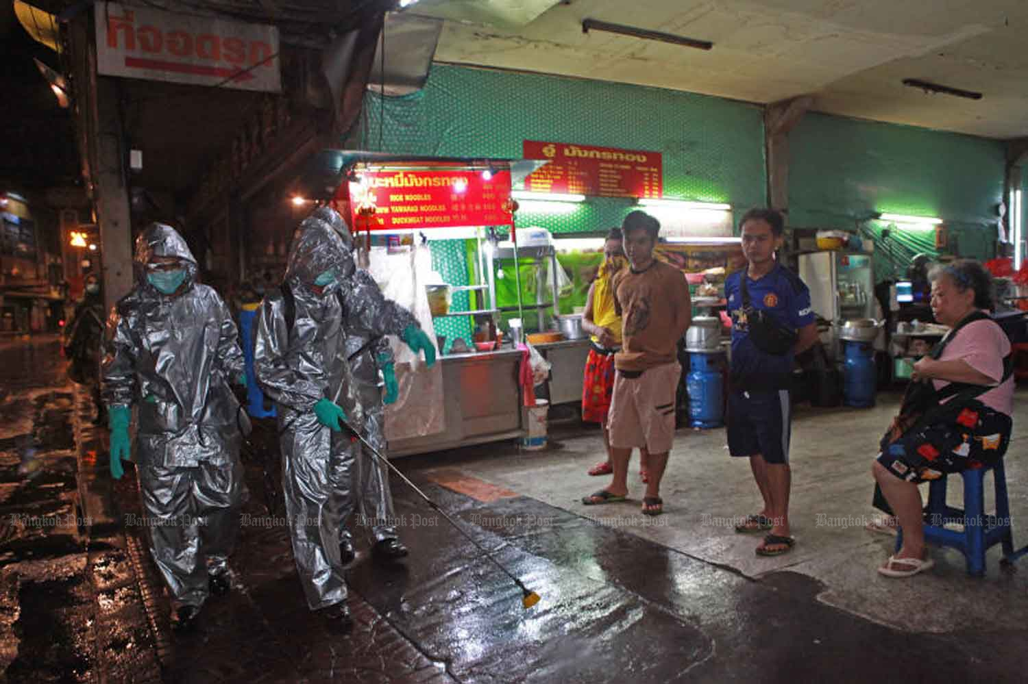 People watch as soldiers in full protective gear spray a disinfectant solution on the footpath in Bangkok's Yaowarat area in the early hours of Thursday. The army will be disinfecting various locations across the city until the end of the month to combat the spread of coronavirus. (Photo by Arnun Chonmahatrakool)