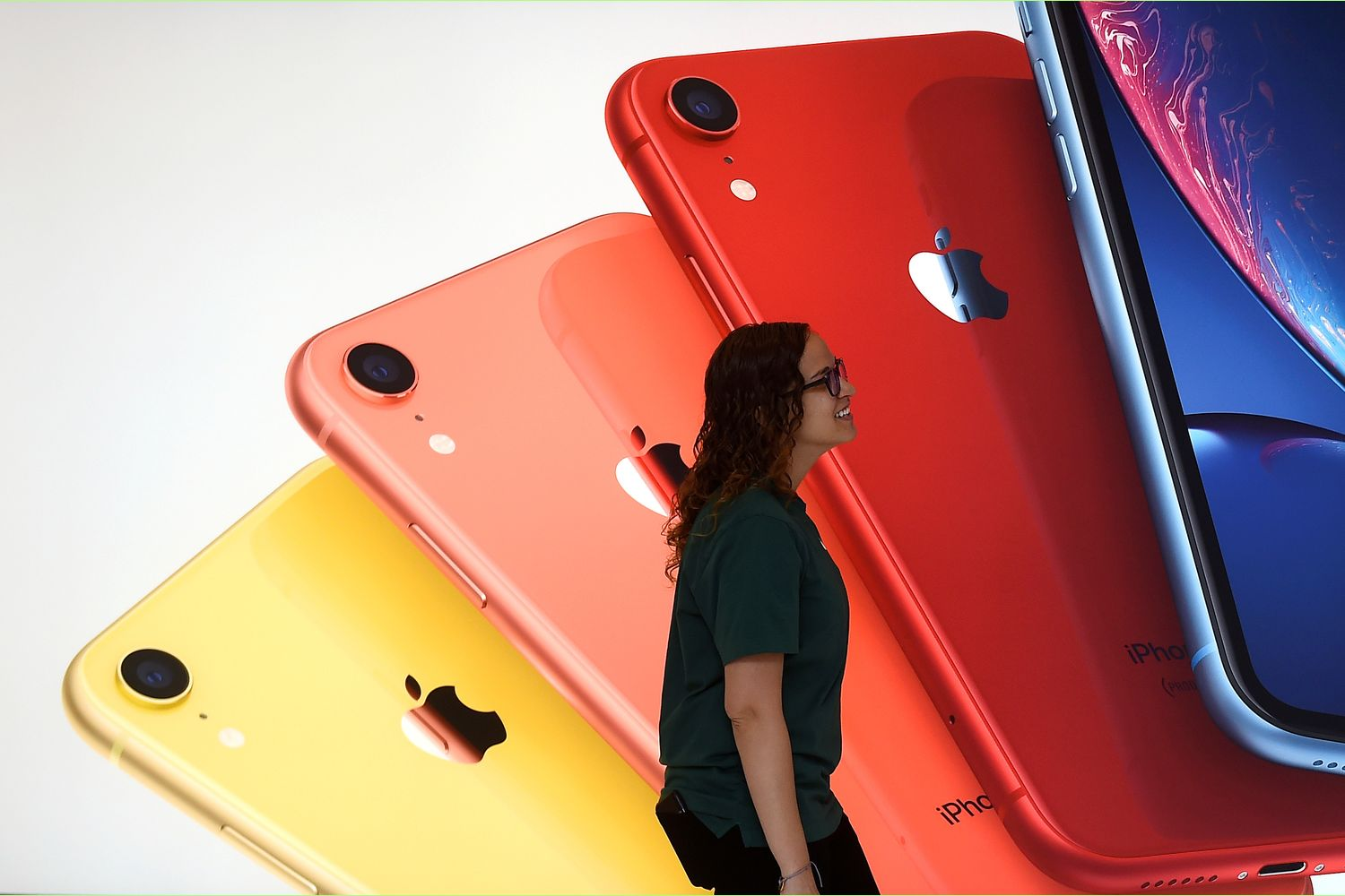 An Apple Store employee walks past an illustration of iPhones at the new Apple Carnegie Library during the grand opening and media preview in Washington in May last year. (Reuters photo)