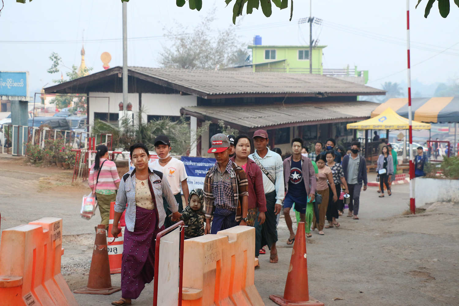 Myanamar nationals cross through the Three Pagodas pass checkpoint to Sangkhla Buri district in Kanchanaburi on Friday before it closes starting from Saturday. (Photo by Piyarach Chongcharoen)