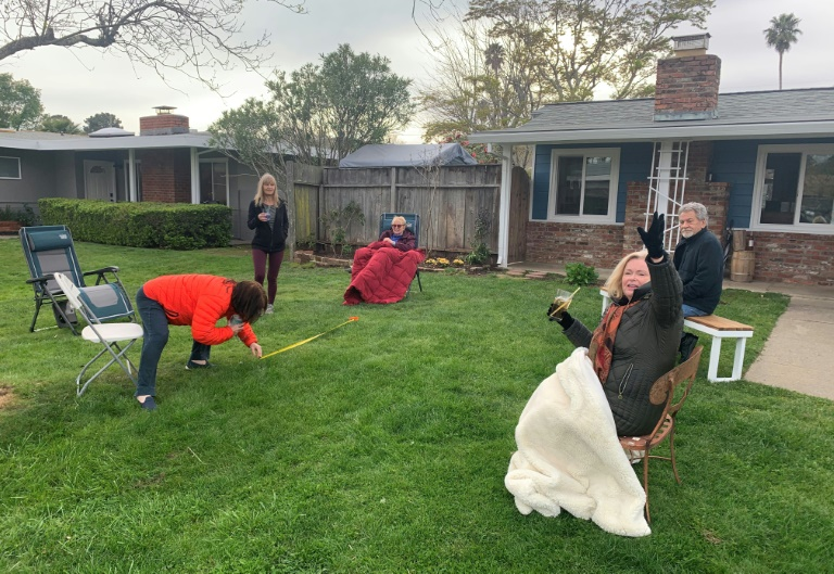 Neighbors hold a six-foot-away party while listening to the song