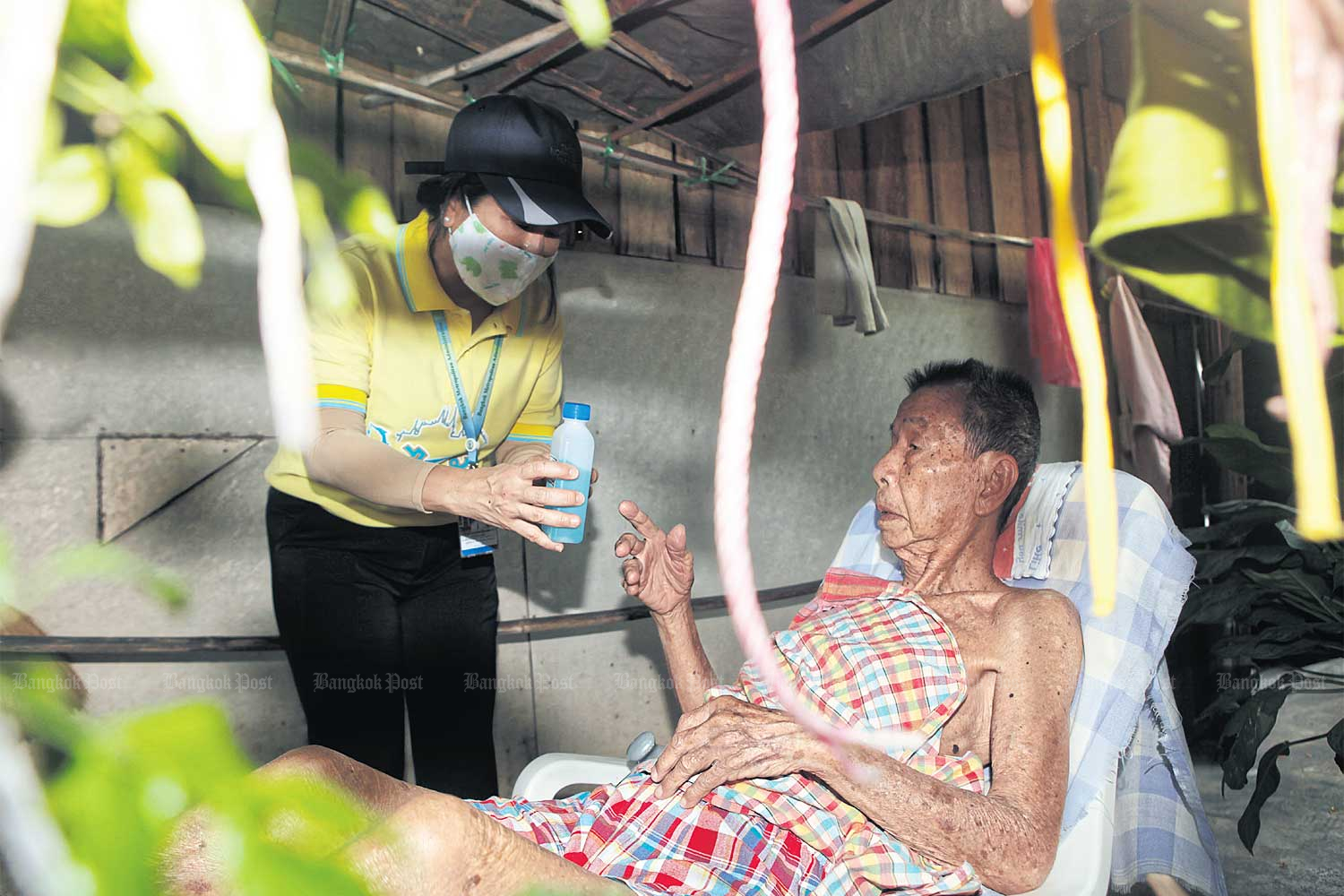 Not for drinking: An official from Dusit district hands a bottle of ethyl alcohol to an elderly resident in Sam Sen community located in Bangkok as a part of campaign to raise awareness about social distancing and personal hygiene to combat the Covid-19 disease. (Photo by Nutthawat Wicheanbut)