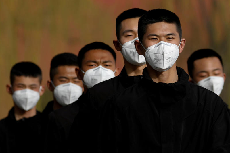 Security personnel wearing face masks to contain the spread of coronavirus disease walk along a street outside the Forbidden City in Beijing on Wednesday. (Reuters photo)