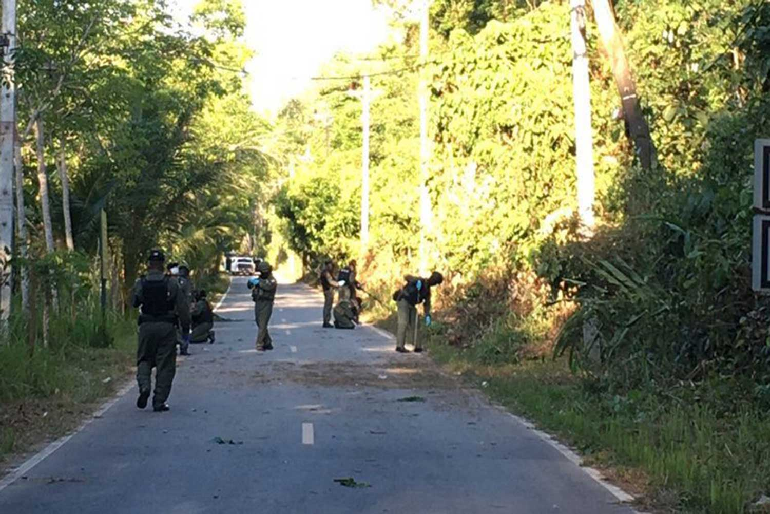Soldiers, police and bomb disposal officers inspect the scene of a bomb blast in Rangae district of Narathiwat on Friday evening. Two rangers were hurt in the explosion. (Photo by Waedao Harai)