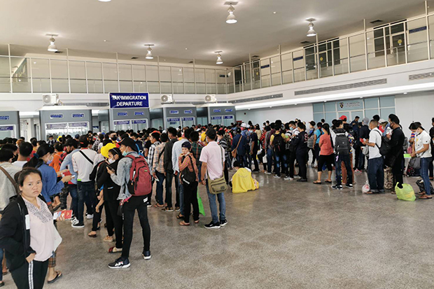 Myanmar nationals throng the checkpoint at the second Thai-Myanmar Friendship Bridge in Mae Sot district on Saturday before the closure of most of the border checkpoints in Tak. (Photo by Assawin Pinitwong)