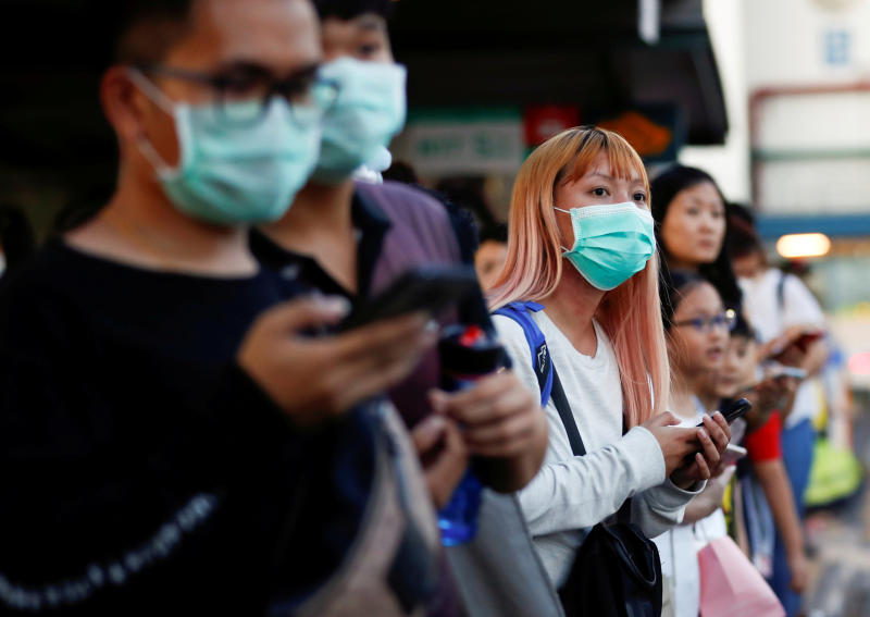 Commuters wait for a transport to leave the Woodlands Causeway across to Singapore from Johor, hours before Malaysia imposes a lockdown on travel due to the coronavirus outbreak on Tuesday. (Reuters photo)