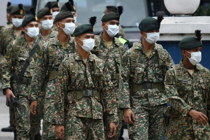 Soldiers wearing facemasks leave a police station to be deployed to man roadblocks during the control of movement in Kuala Lumpur on Sunday amid fears over the spread of the Covid-19 novel coronavirus. (AFP photo)