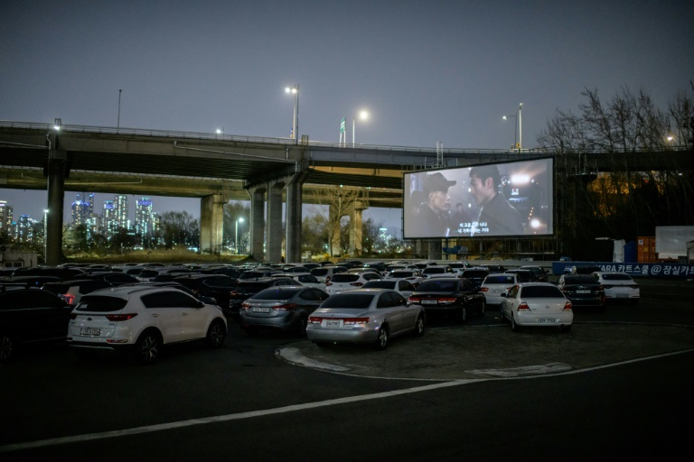 People can park their cars in front of a large outdoor screen.