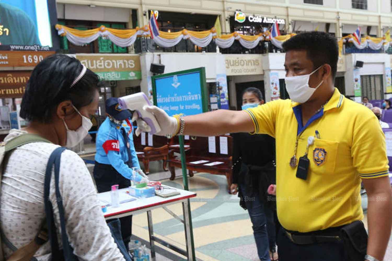 An official checks the body temperature of a traveller at the Hua Lamphong railway terminus in Bangkok on Monday as local cases of Covid-19 soared by 122. (Photo: Wichan Charoenkiatpakul)