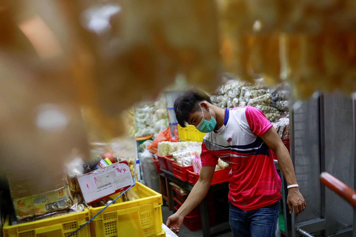 A migrant worker from Myanmar wears a protective face mask due to the coronavirus disease outbreak, as he works in a market in Bangkok on Friday. (Reuters photo)