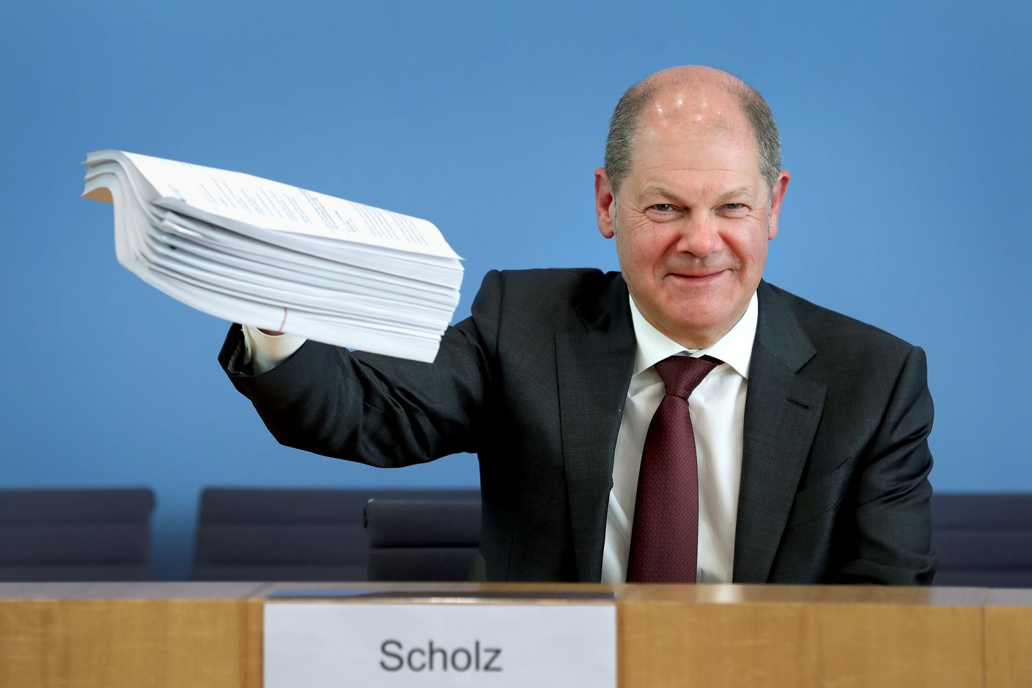 German Finance Minister Olaf Scholz holds a stack of files during a joint news conference with Economy Minister Peter Altmaier to reveal details of a supplementary budget to counter the impact of the coronavirus outbreak, in Berlin, on Monday. (Michael Sohn/Pool via Reuters)