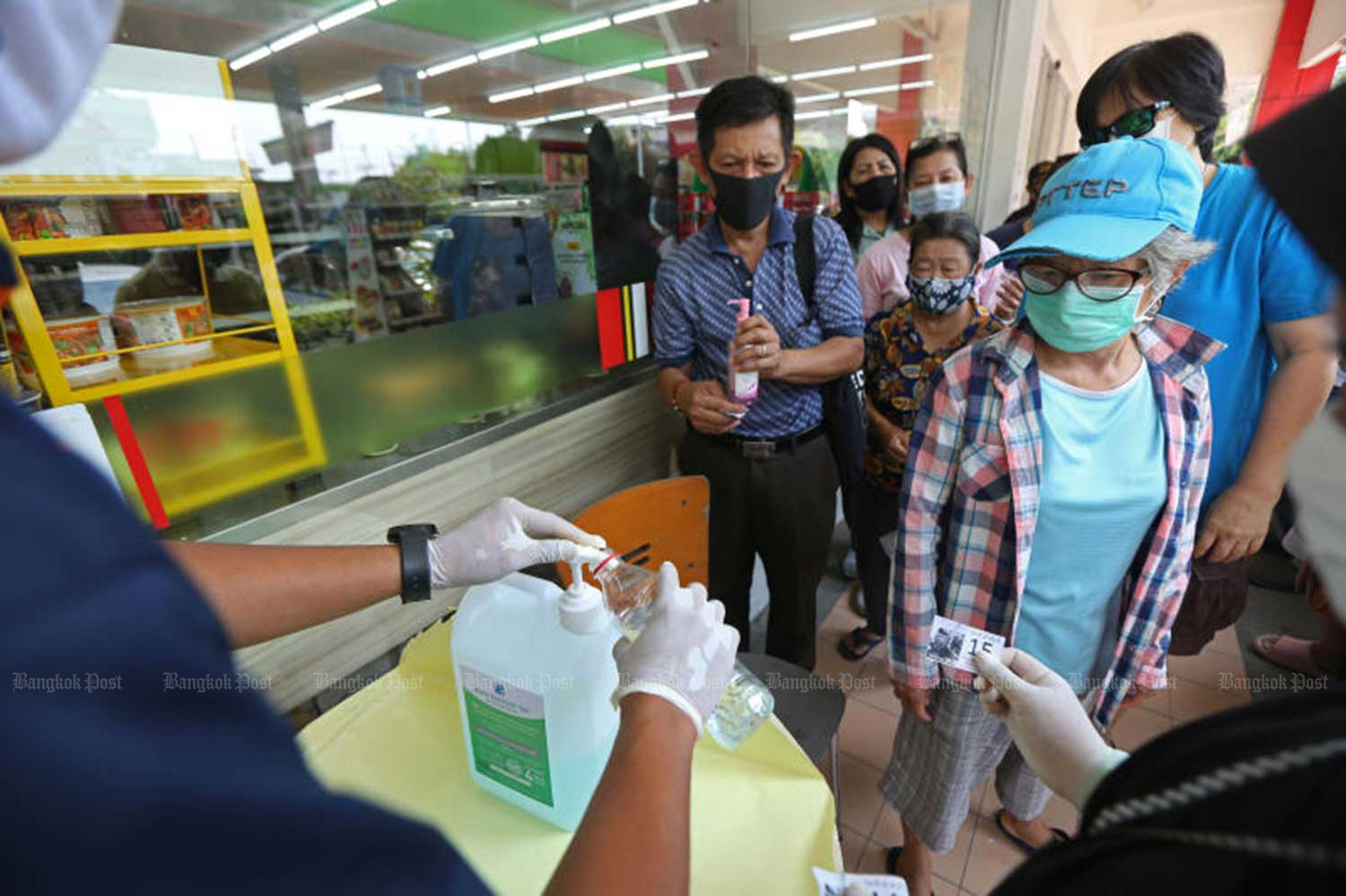 Alcohol gel is given free of charge to people at the Bang  Chak petrol station on Sukhaphiban 1 Road. (Photo by Varuth Hirunyatheb)