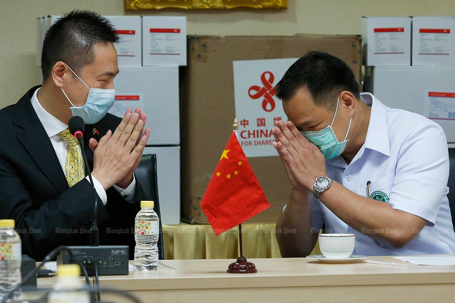 Wais for supplies: Public Health Minister Anutin Charnvirakul performs a wai to express his gratitude to Yang Xin, Charge d'Affaires for the Chinese embassy in Bangkok, for China's donations of medical supplies which have just arrived in Thailand. (Photo by Pattarapong Chatpattarasill)
