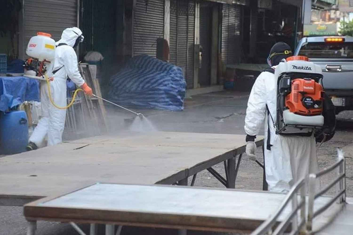 Municipal workers spray disinfectant at a marketplace in Ayutthaya's Muang district as a precaution against Covid-19. (Photo: Sunthorn Pongpao)
