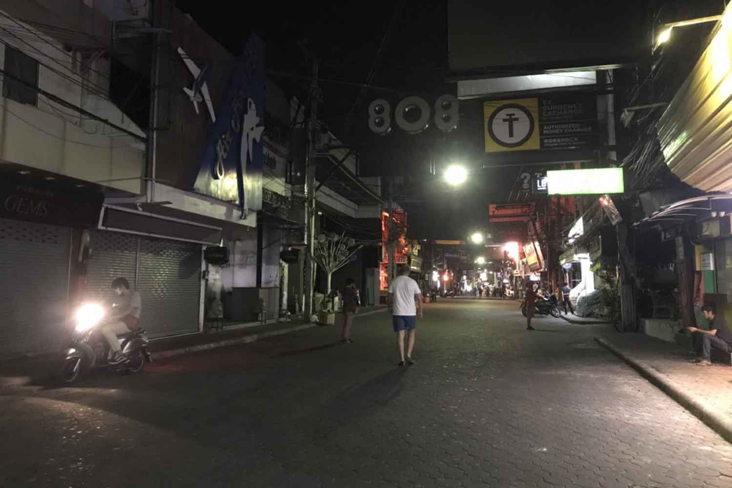 A usually busy street in Pattaya is quiet, almost deserted on Tuesday night after entertainment venues were closed because of Covid-19 disease. (Photo: Chaiyot Pupattanapong)