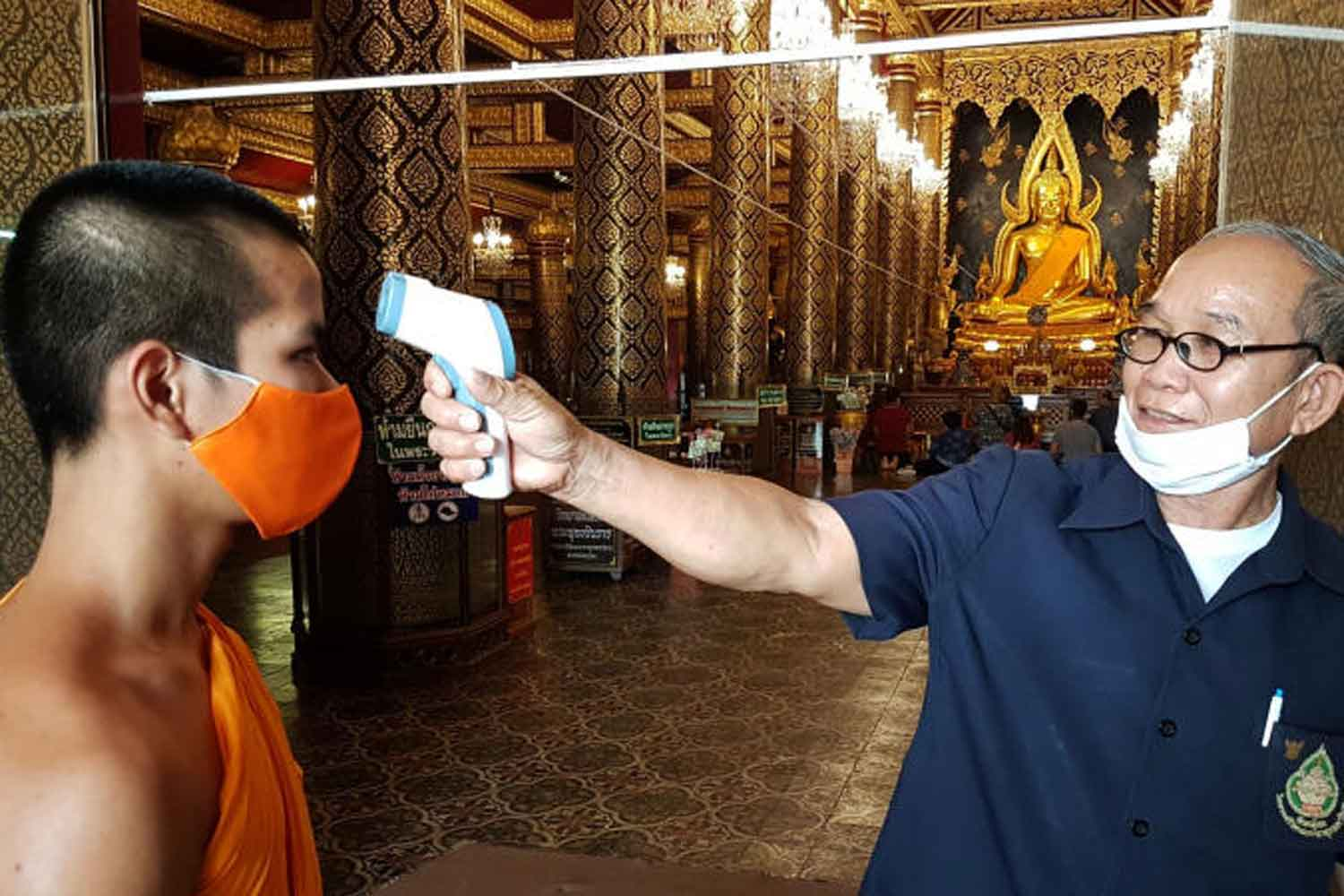 An official measures the body temperature of a monk at Wat Phra Si Rattana Mahathat in Muang district of Phitsanulok province on Tuesday. The Public Health Ministry on Wednesday reported 107 more local cases of Covid-19. (Photo: Chinnawat Singha)