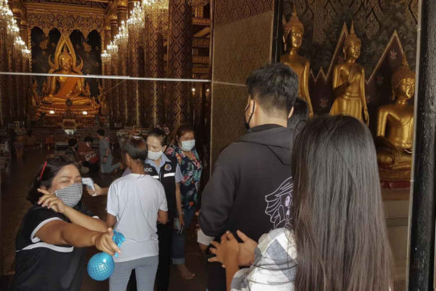 Health officials and volunteers spray disinfectant on visitors to Wat Phra Si Rattana Mahathat in Muang district of Phitsanulok on Tuesday. (Photo: Chinnawat Singha)