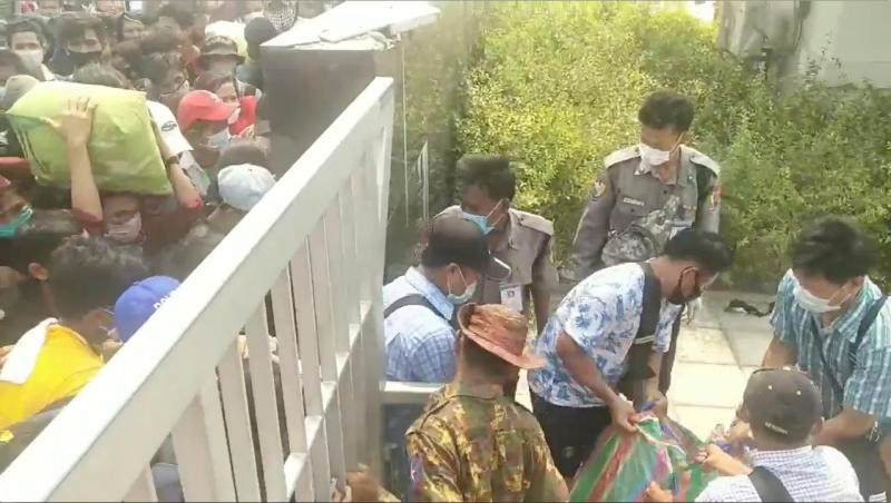 Migrant workers from Myanmar carry bags as they enter a border gate on the Myanmar-Thai Friendship Bridge into Myawaddy, Myanmar, as they leave Thailand due to the coronavirus disease outbreak on Tuesday in this still image from video obtained via social media. (THANT ZIN AUNG via REUTERS)