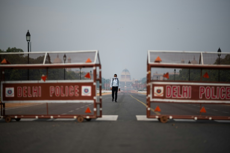 A man walks on a deserted road in New Delhi during an Indian government-imposed lockdown against Covid-19.