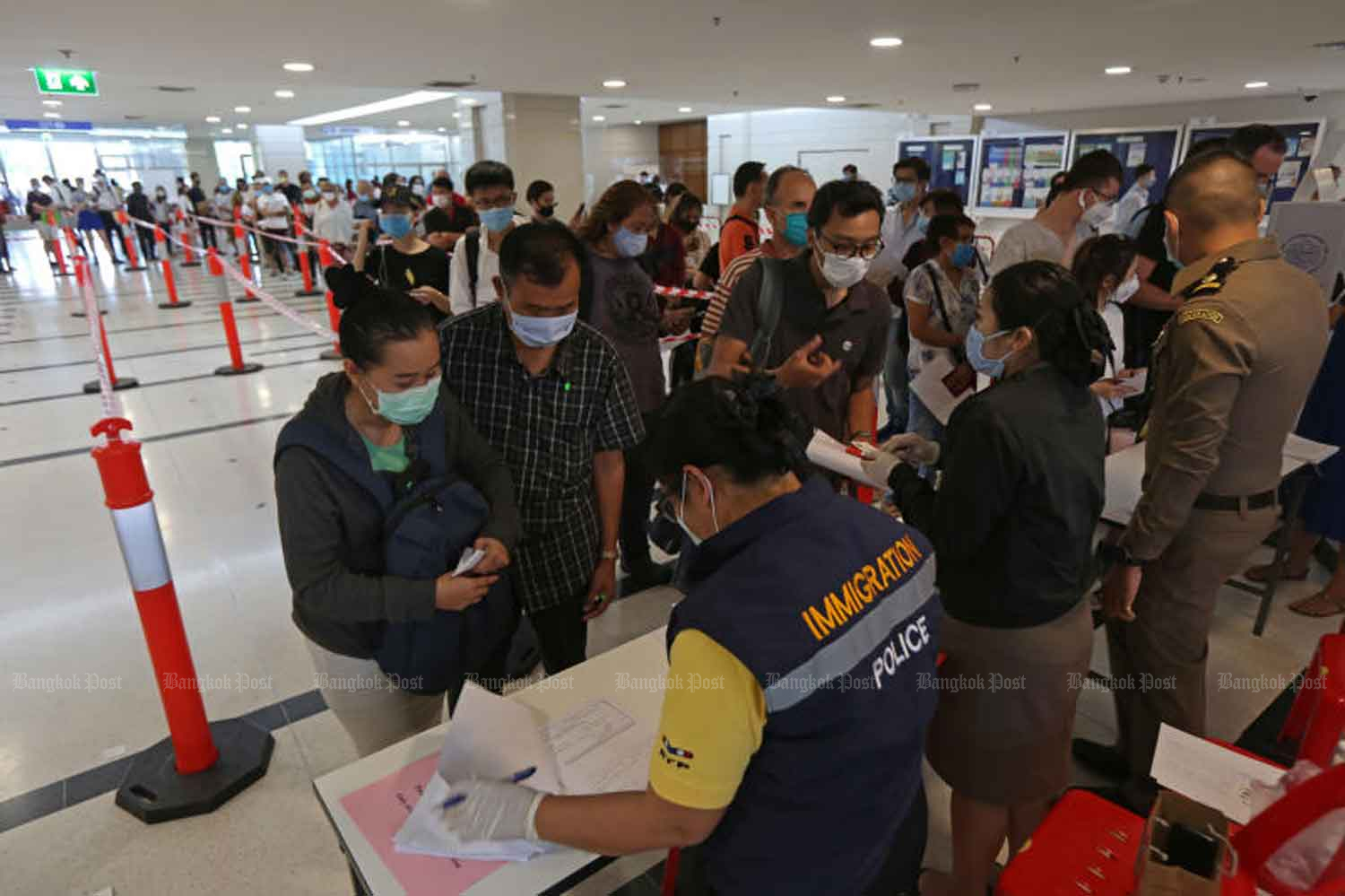 Foreigners report to the Immigration Bureau on Chaeng Watthana Road in Laksi district of Bangkok on Tuesday. (Photo: Varuth Hirunyatheb)