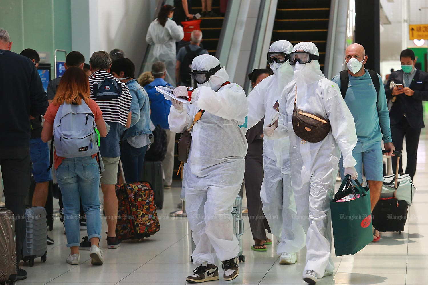 Tourists wear protective suits and goggles as they queue to board flights at Suvarnabhumi Airport. (Photo by Somchai Poomlard)