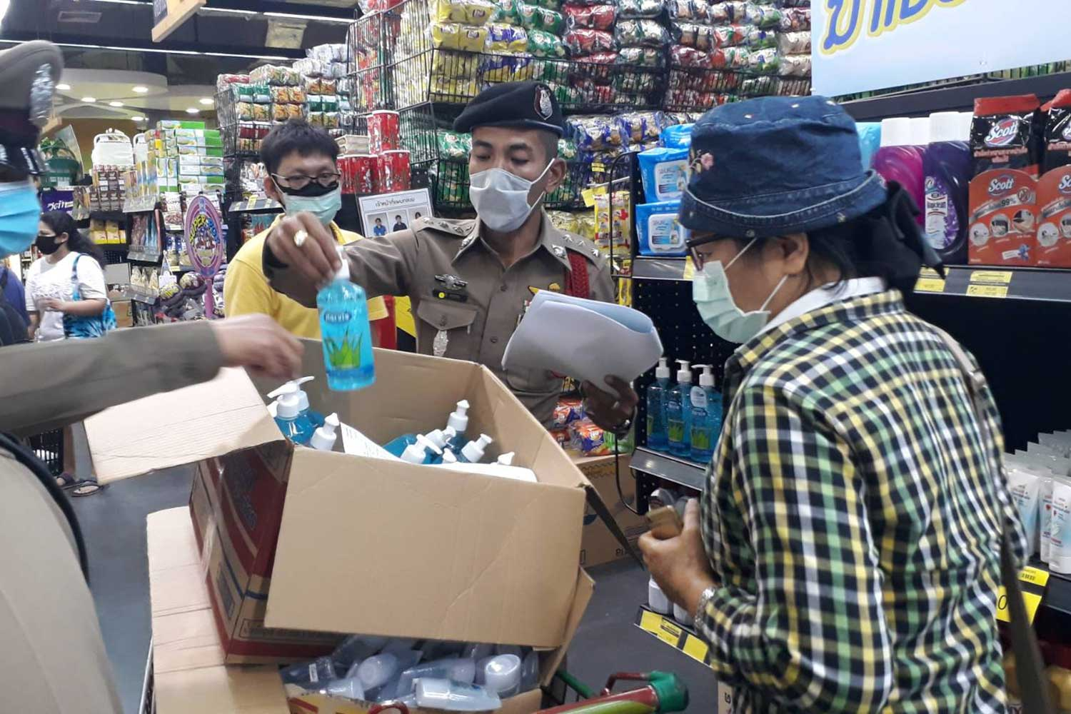 A police officer looks at a bottle of alcohol gel at Phuket Grocery in Phuket during the  raid on Thursday morning. Many products suspected of being sold at inflated prices were seized and the store manager held for questioning. (Photo: Achadtaya Chuenniran)