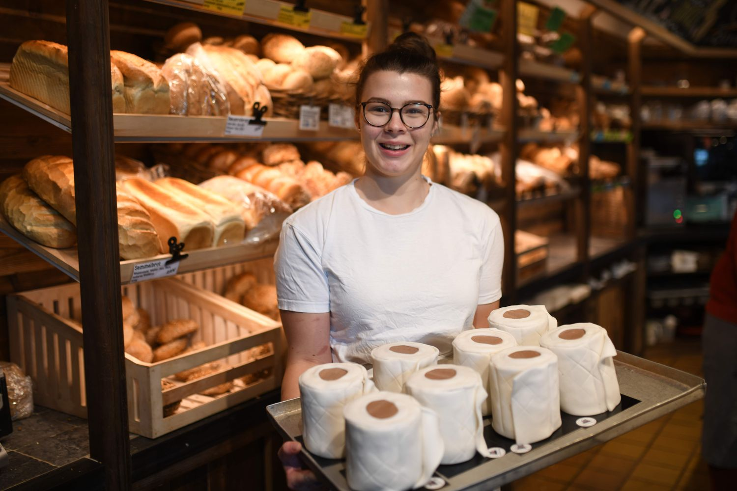 Apprentice Andrea Schulz presents a tablet with toilet paper-shaped cakes at the bakery Schuerener Backparadies in Dortmund, western Germany, on Thursday. The bakery of owner Tim Kortuem sells toilet paper cakes, which are spread with cream and wrapped in fondant. The sweet toilet paper rolls have become a 'bestseller' during the virus crisis. (AFP photo)