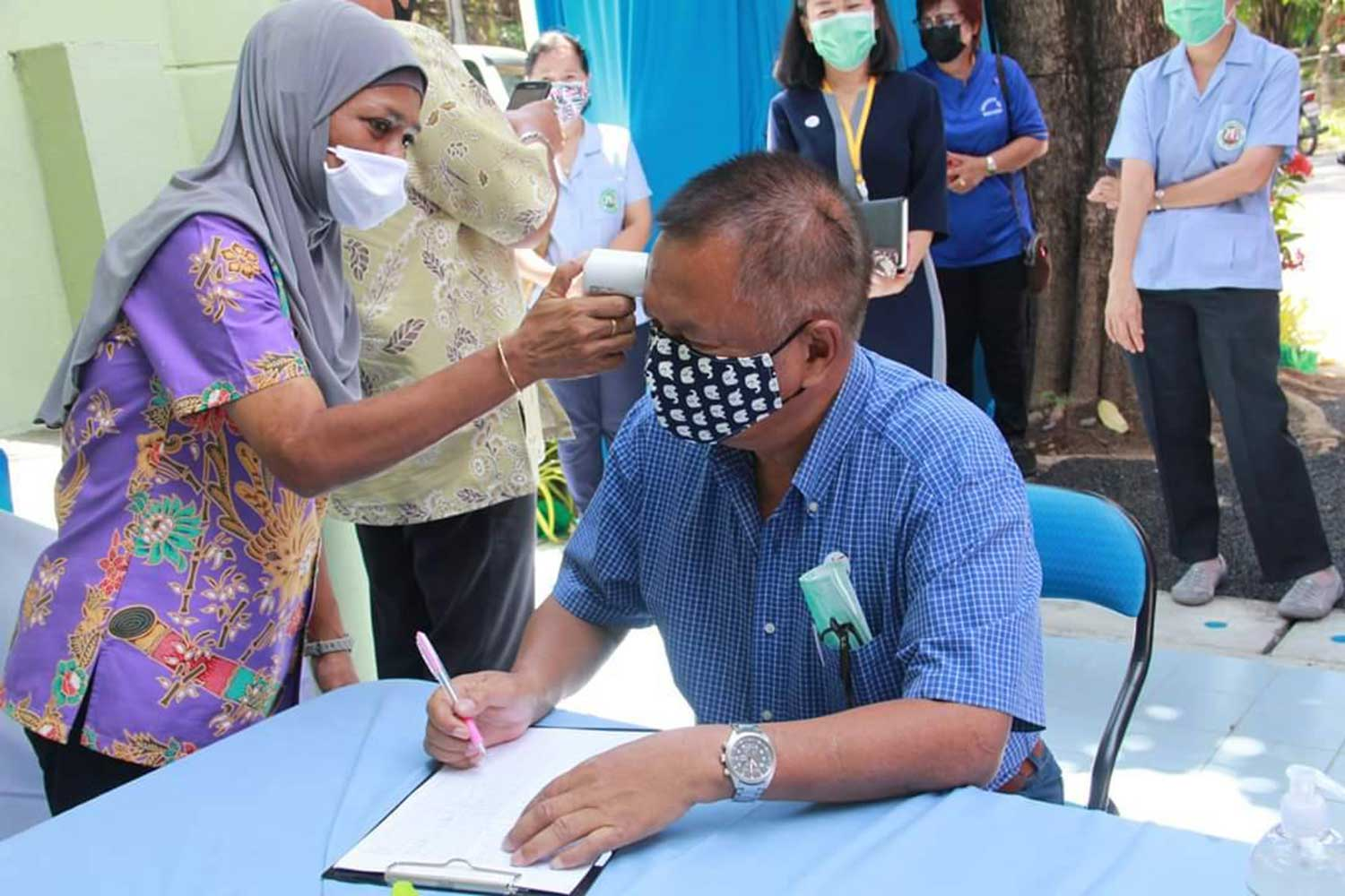 An official checks the body temperature of a man in Phuket. The island province on Thursday reported five new coronavirus infections, bringing the total to 34. (Photo: Achadtaya Chuenniran)