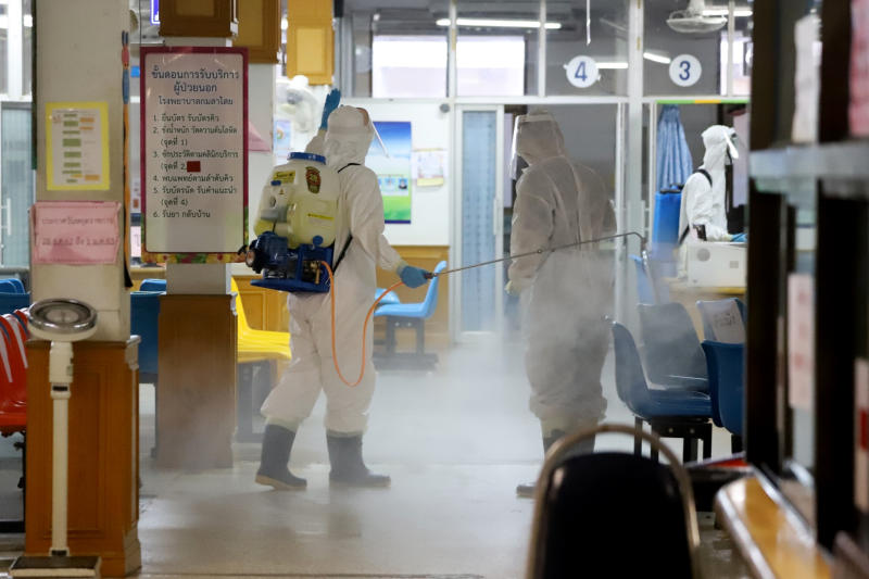 Officials spray Kamalasai Hospital in Kamalasia district of Kalasin with disinfectant on Tuesday. (Photo by Yongyuth Phuphuangphet)
