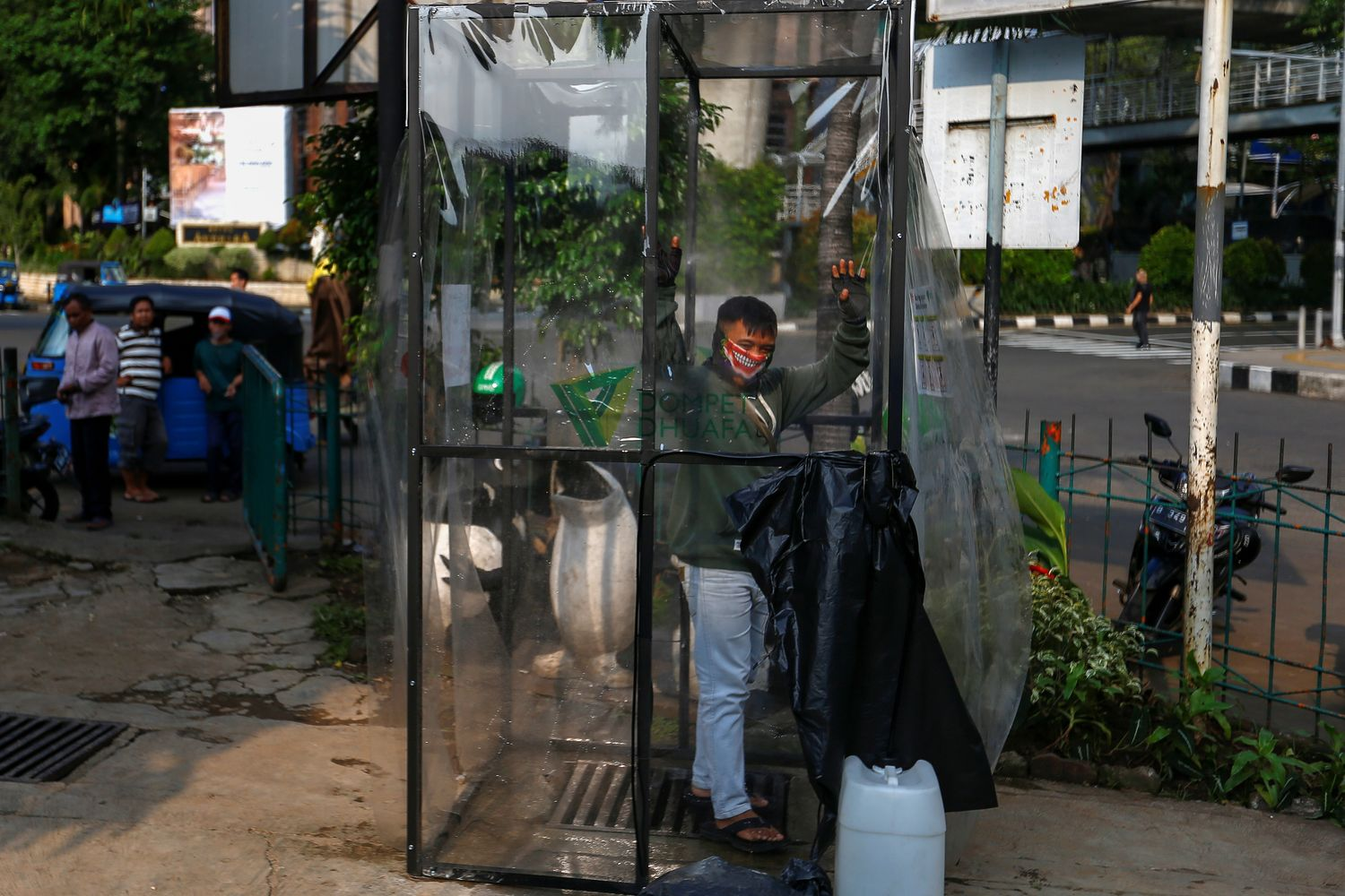 A man wearing a face mask is sprayed inside a disinfection chamber outside a shopping mall after Jakarta begins a two-week emergency period to prevent the spread of the disease in Jakarta on Wednesday. (Reuters photo)
