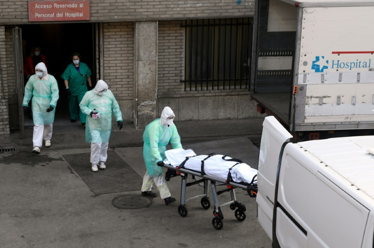 A health worker carries a body on a stretcher outside Gregorio Maranon hospital in Madrid, Spain. (Photo: AFP)