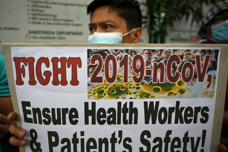 A health worker wearing a face mask holds a placard during a protest in front of a government hospital in Manila.
