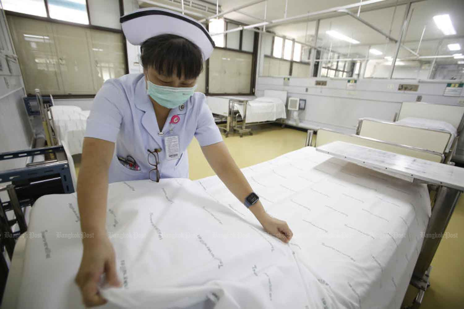 A nurse straightens sheets on beds to accommodate Covid-19 patients at Rajavithi Hospital. The hospital, one of the country's largest and best equipped, has been chosen to set standards for state-run hospitals in the transfer and screening of Covid-19 patients. (Photo: Pornprom Satrabhaya)