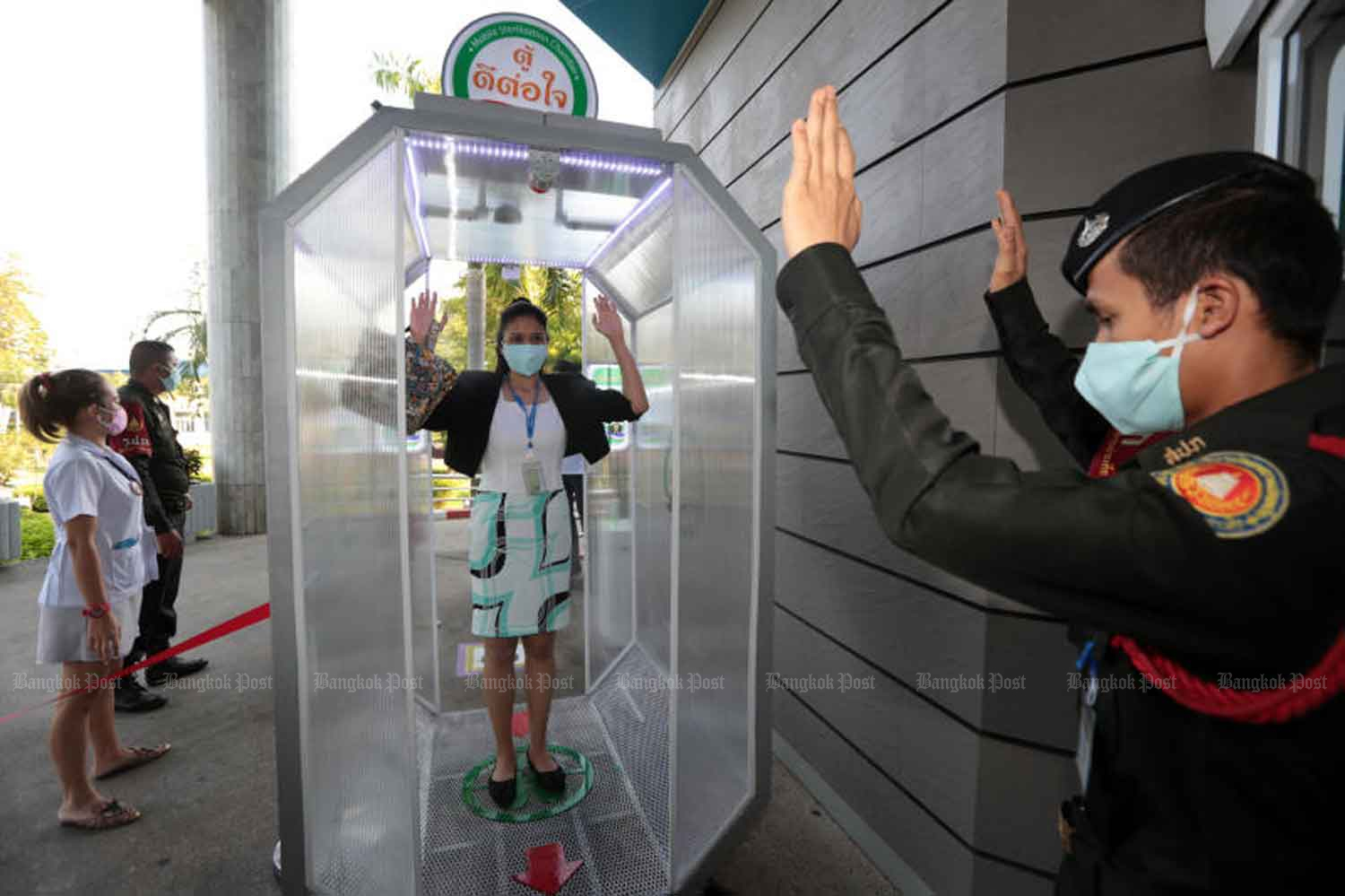 A security official shows a woman how to use a cubicle equipped with disinfectant spray for people entering Srithanya Hospital in Nonthaburi province. The cubicle, donated by a private business, is for use on people who have gone through a thermal scan. (Photo: Chanat Katanyu)