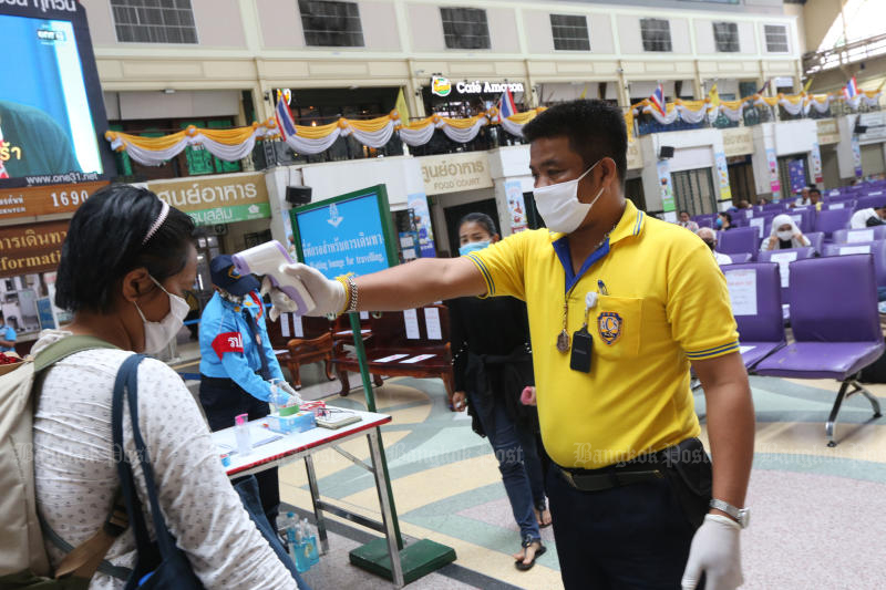 A State Railway of Thailand official checks the temperature of a passenger at Hua Lumphong station. (Photo: Wichan Charoenkiatpakul)