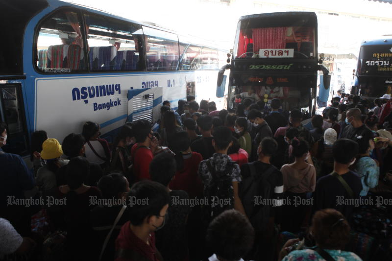 Travellers wait to board their buses at the crowded Mor Chit bus terminal in Bangkok on Tuesday. (Photo by Nutthawat Wicheanbut)