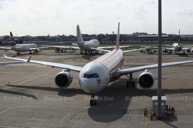 A Thai AirAsia plane sits on the tarmac at Don Mueang airport on Friday. (Photo by Pattarapong Chatpattarasill)