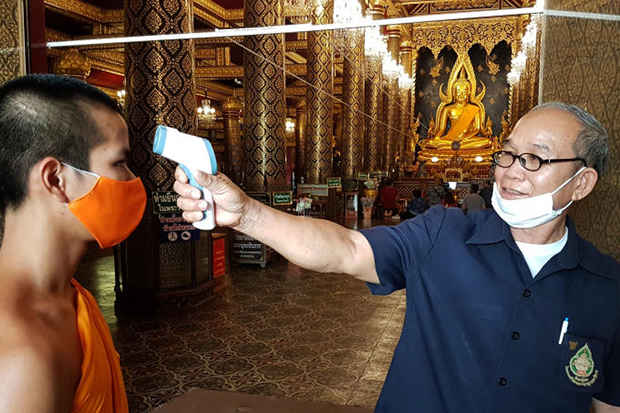 A health official checks the temperature of a monk before he enters the chapel at Wat Phrasrimahathat in Muang district of Phitsanulok province on Tuesday. (Photo by Chinnawat Singha)