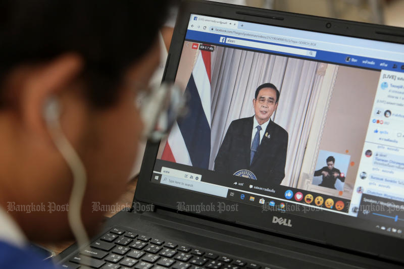 A reporter at Government House listens to Prime Minister Prayut Chan-o-cha's announcement on the enforcement of the emergency decree at Government House on Wednesday. (Photo by Chanat Katanyu)