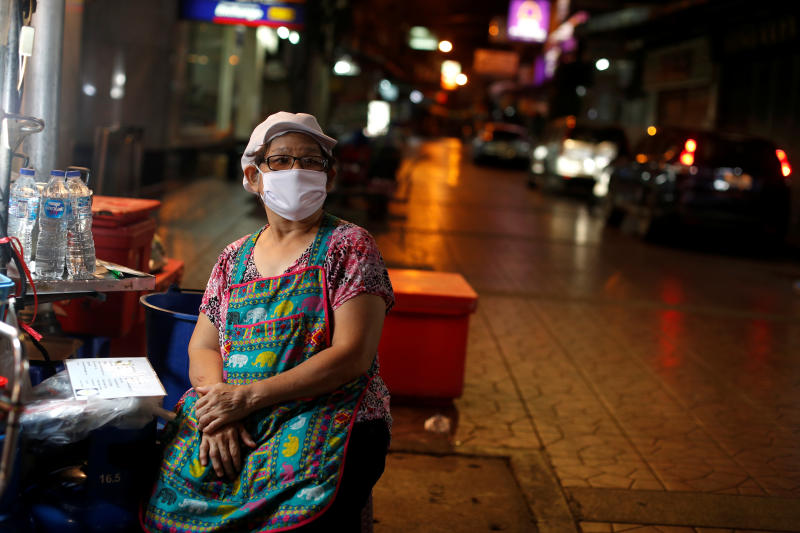 A woman wearing a mask waits for customers at an empty food stall during the coronavirus disease outbreak in Yaowarat, Bangkok on Friday. (Reuters photo)