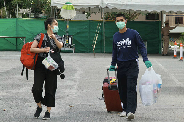 A student (left) leaves a reception facility of the Royal Thai Navy in Satthahip, Chon Buri after she and 82 others completed a 14-day quarantine on Sunday. (Royal Thai Navy photo)