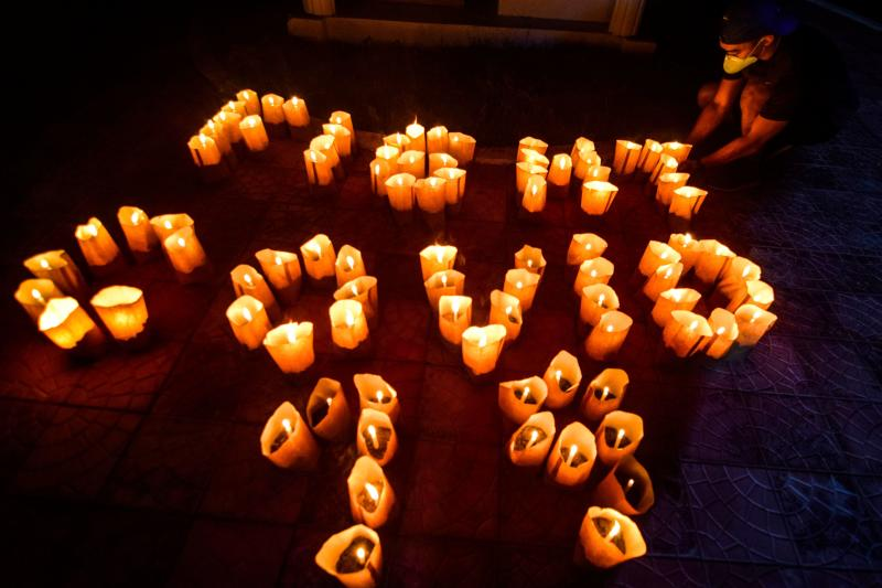 A volunteer arranges lit candles in a formation to read
